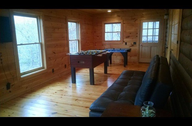 Spacious Rec Room with TV, Foosball, Air Hockey, and access to lower balcony and steps to the firepit area